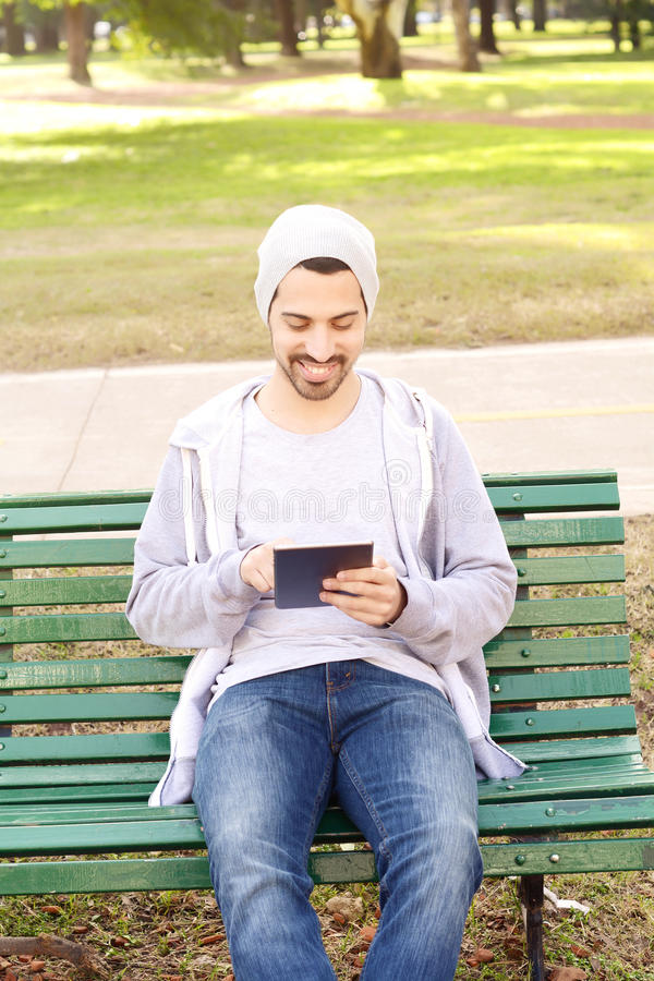Junger Mann, der die Tablette sitzt auf Parkbank verwendet lizenzfreie stockbilder