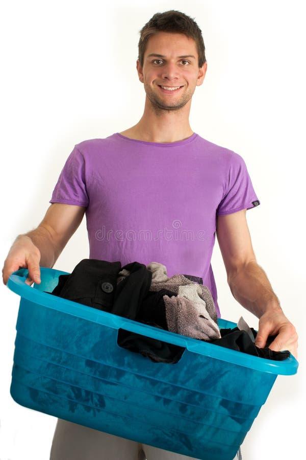 Junger Mann, der die Wäscherei tut stockfotografie