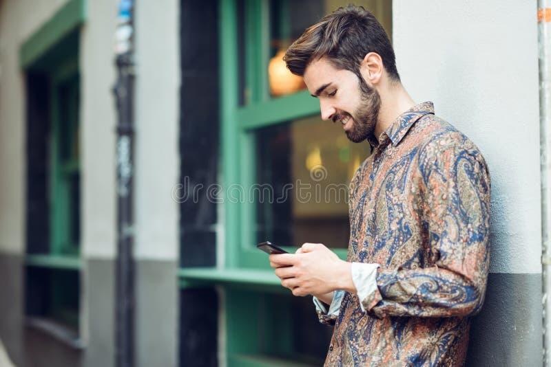 Junger Mann, der die zufällige Kleidung betrachtet seinen Smartphone im Th trägt lizenzfreie stockfotos