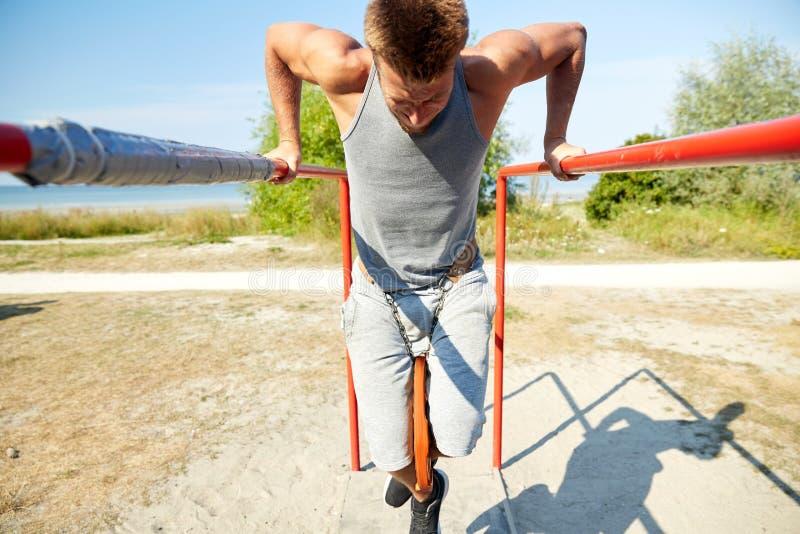 Junger Mann, der draußen auf Barren trainiert lizenzfreies stockbild