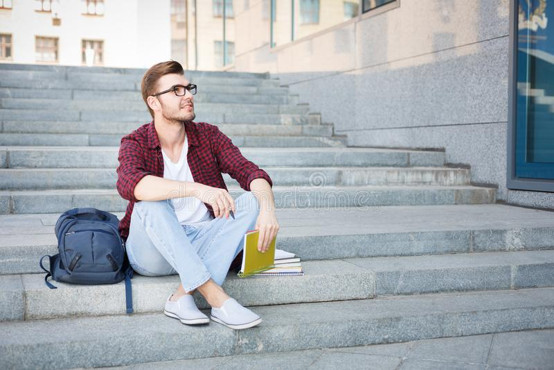 Junger Mann, der draußen auf der Treppe mit Notizbuch sitzt stockbilder