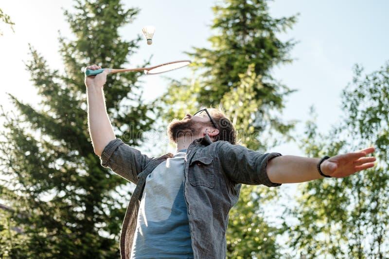 Junger Mann, der draußen Badminton im Park spielt Konzept eines aktiven und gesunden Lebensstils lizenzfreies stockfoto