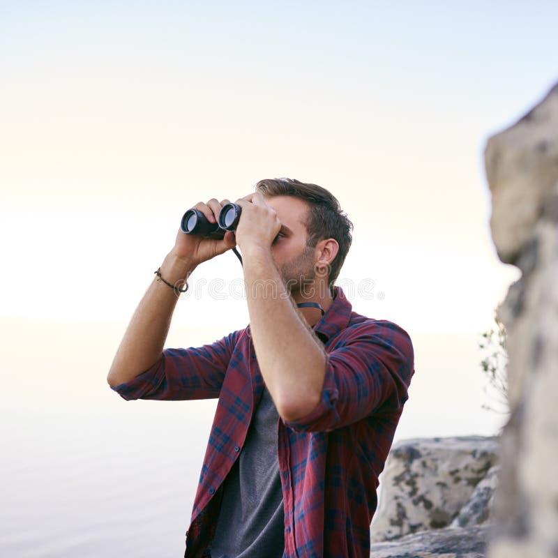 Junger Mann, der draußen Ferngläser für birdwatching verwendet lizenzfreies stockbild