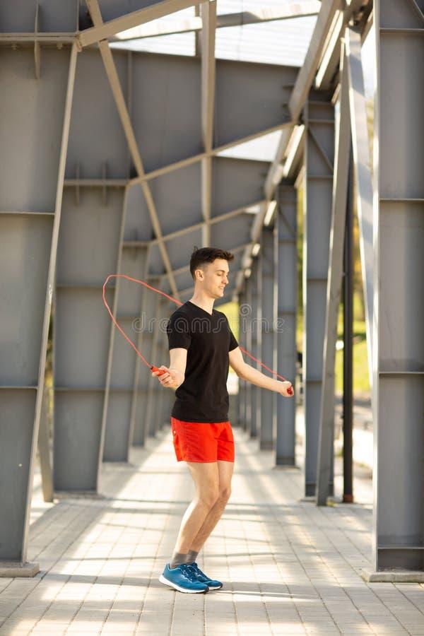 Junger Mann, der drau?en mit Seilspringen ?berspringt Trainieren und Lebensstilkonzept lizenzfreie stockbilder