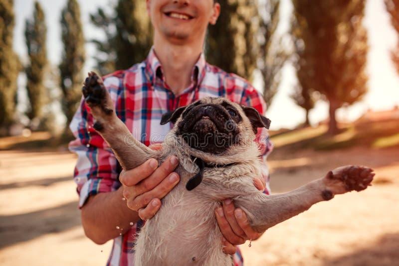 Junger Mann, der draußen Pughund hält Glücklicher Welpe, der mit Meister spielt Spaß mit Haustier haben lizenzfreie stockfotografie