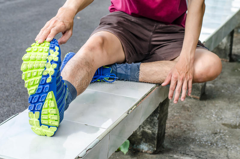 Junger Mann, der draußen seine Beine ausdehnt lizenzfreies stockfoto