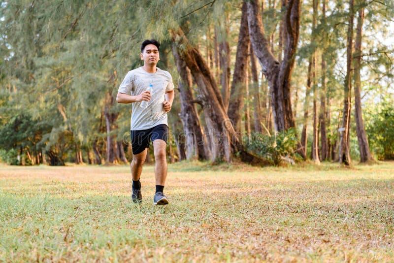 Junger Mann, der draußen Training der Park rüttelt und tut lizenzfreies stockbild