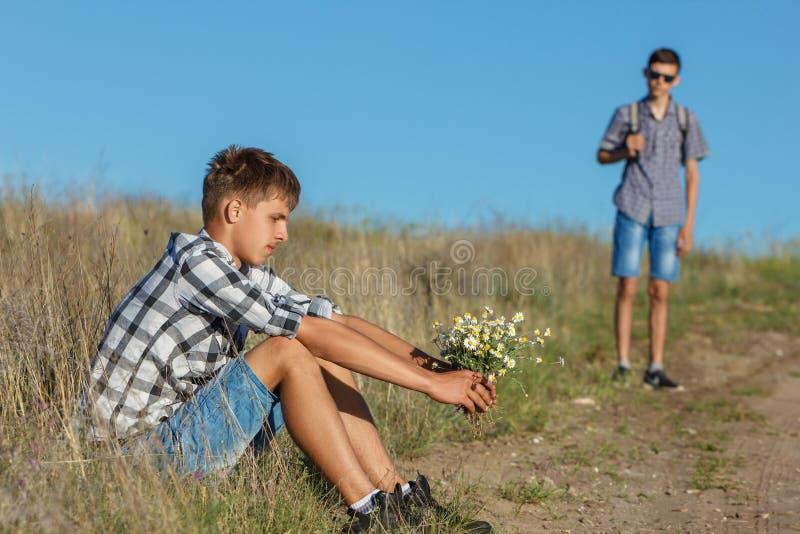 Junger Mann, der durch die Straße mit den Blumen, auf andere wartend, das Konzept des Verhältnisses sitzt stockbilder