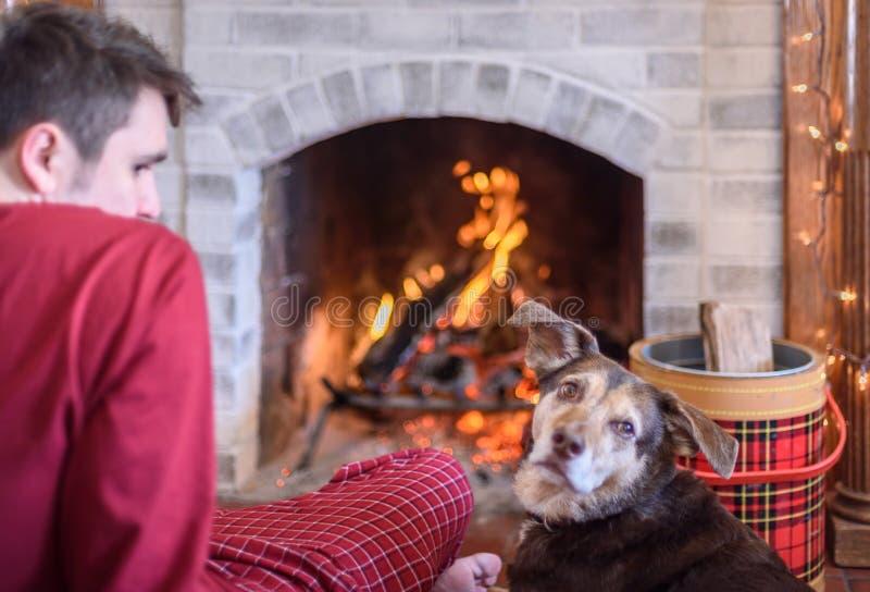 Junger Mann, der durch Feuer mit Hund sitzt stockfotografie