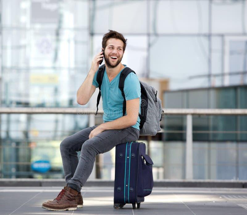 Junger Mann, der durch Handy am Flughafen nennt lizenzfreie stockfotografie