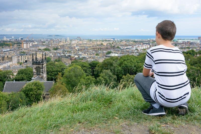 Junger Mann, der Edinburgh von Calton-Hügel betrachtet stockfotos