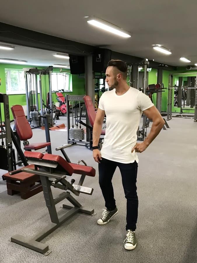JungerMann Â, der an Eignung in der athletischen Hallensporttrainer Fitness-Ausrüstung teilnimmt, motiviert, um Sport zu machen stockfotos
