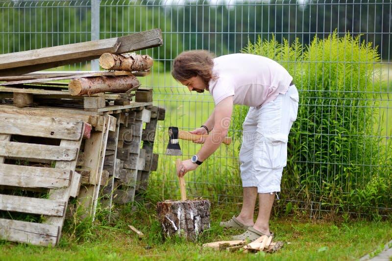Junger Mann, der ein Brennholz mit einer Axt hackt stockbilder