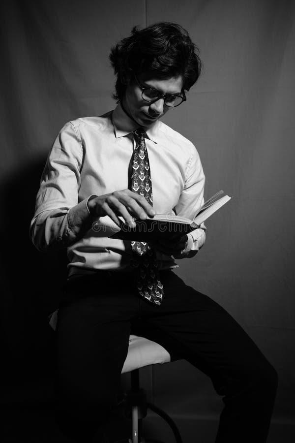 Junger Mann, der ein Buch mit Gläsern liest stockbilder