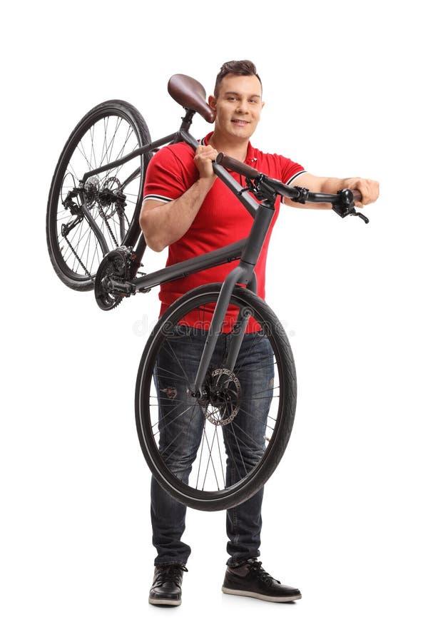 Junger Mann, der ein Fahrrad auf seiner Schulter hält lizenzfreie stockbilder