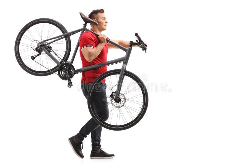Junger Mann, der ein Fahrrad auf seiner Schulter trägt stockfotografie