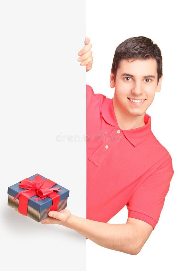 Junger Mann, der ein Geschenk und eine Stellung hinter Panel anhält stockfotos