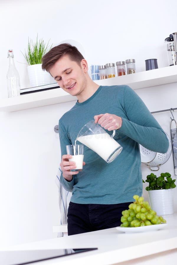 Junger Mann, Der Ein Glas Milch In Der Küche Trinkt