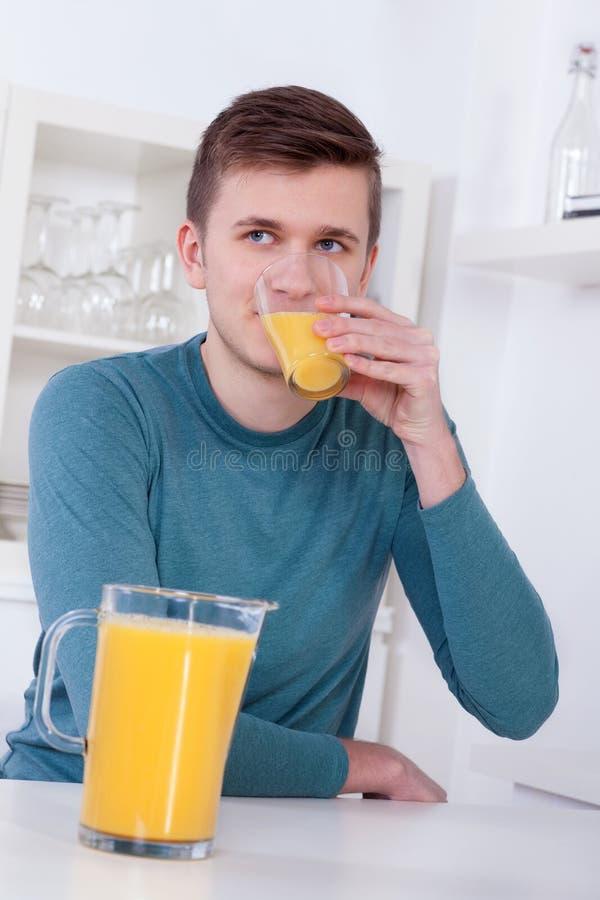 Junger Mann, der ein Glas Orangensaft trinkt stockfoto