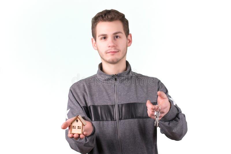 Junger Mann, der ein kleines Holzhaus und Schlüssel hält Lokalisiert auf Weiß lizenzfreies stockfoto