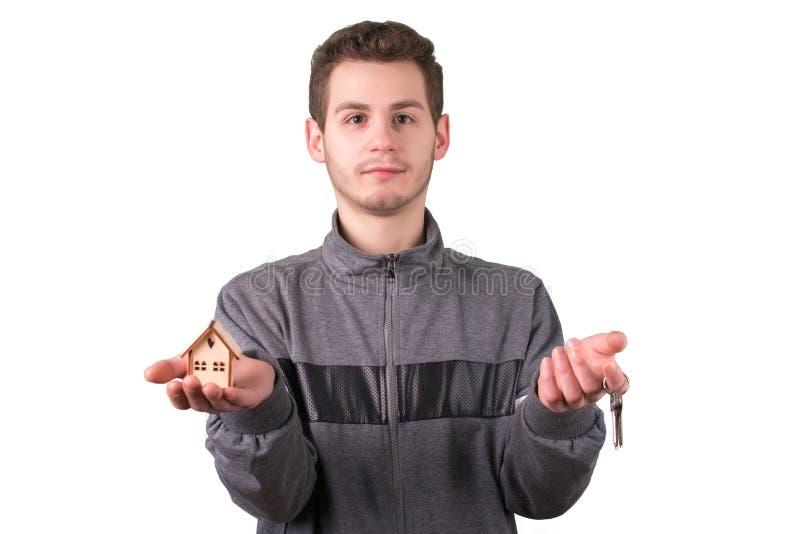 Junger Mann, der ein kleines Holzhaus und Schlüssel hält Lokalisiert auf Weiß stockfotos