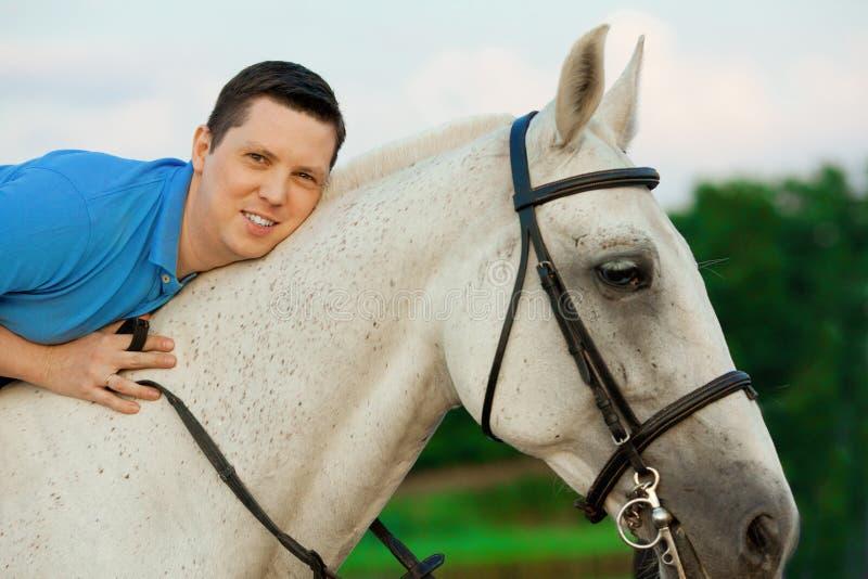 Junger Mann, der ein Pferd bei Sonnenuntergang auf den Strand reitet Mann mit hors lizenzfreie stockfotografie