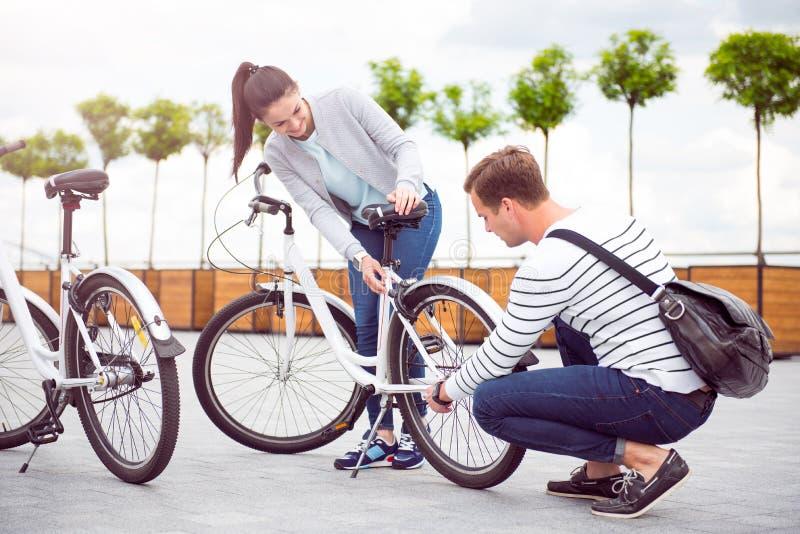 Junger Mann, der ein Rad des Fahrrades repariert stockbilder