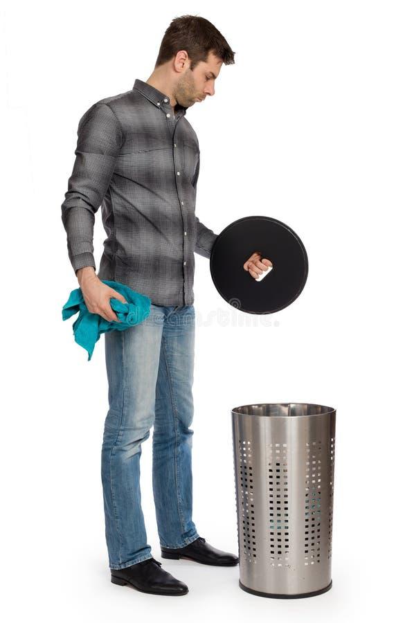 Junger Mann, der ein schmutziges Tuch in einen Wäschekorb einsetzt lizenzfreie stockfotos