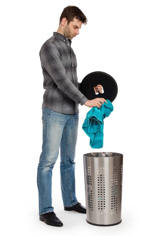 Junger Mann, der ein schmutziges Tuch in einen Wäschekorb einsetzt stockbild