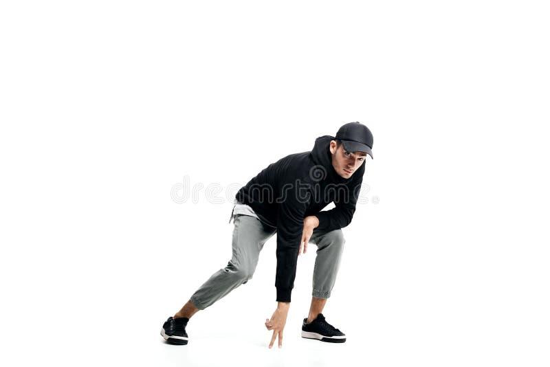Junger Mann, der ein schwarzes Sweatshirt, grauen Hosen, eine Kappe und Turnschuhe tanzen Straßentänze auf einem weißen Hintergru lizenzfreies stockfoto