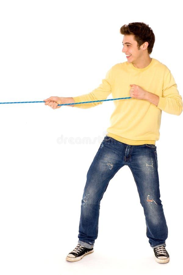 Junger Mann, der ein Seil zieht stockfotos