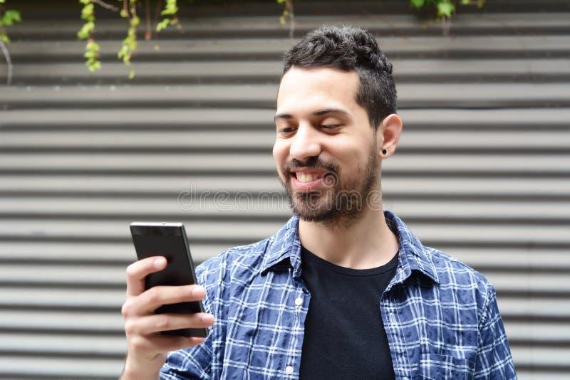 Junger Mann, der ein smartphone verwendet stockfotos
