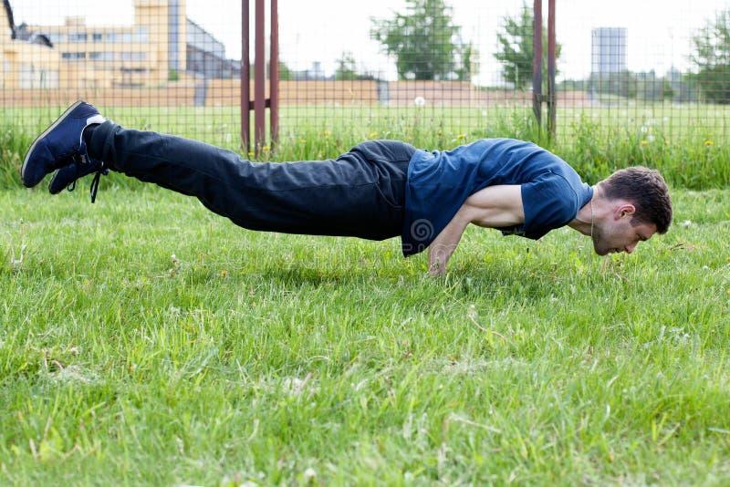 Junger Mann, der eine Übung im Stadtpark tut lizenzfreies stockbild