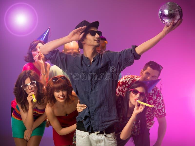 Junger Mann, der eine Discokugel an der Partei anhält lizenzfreie stockfotos