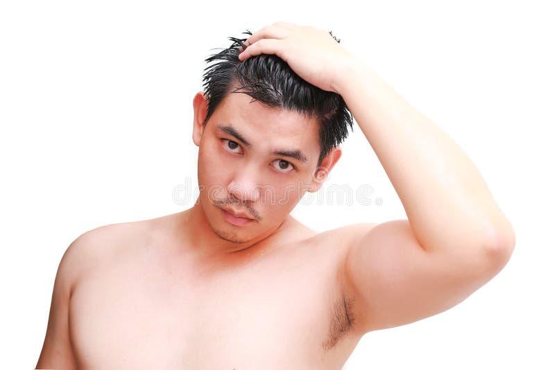 Junger Mann, der eine Dusche und eine Stellung unter flüssigem Wasser im Badezimmer nimmt lizenzfreie stockfotos