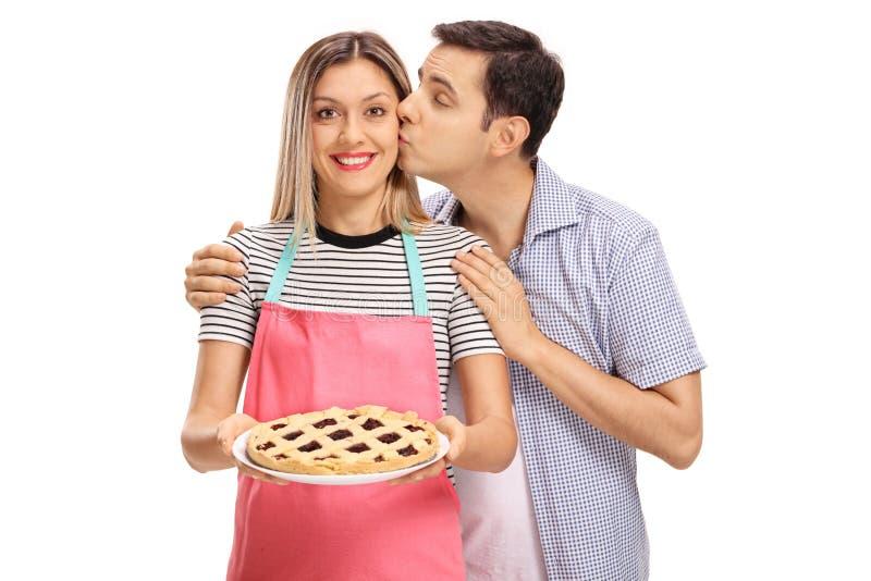 Junger Mann, der eine Frau hält eine frisch gebackene Torte küsst stockfotos