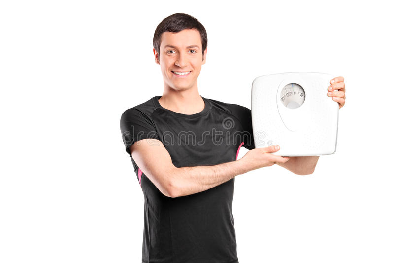 Junger Mann, der eine Gewichtsskala hält lizenzfreies stockbild