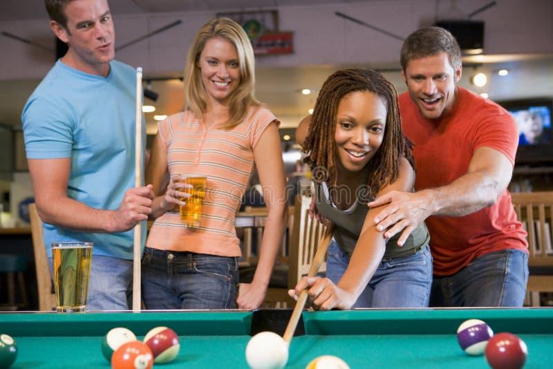Junger Mann, der eine junge Frau unterrichtet, Pool zu spielen stockbilder