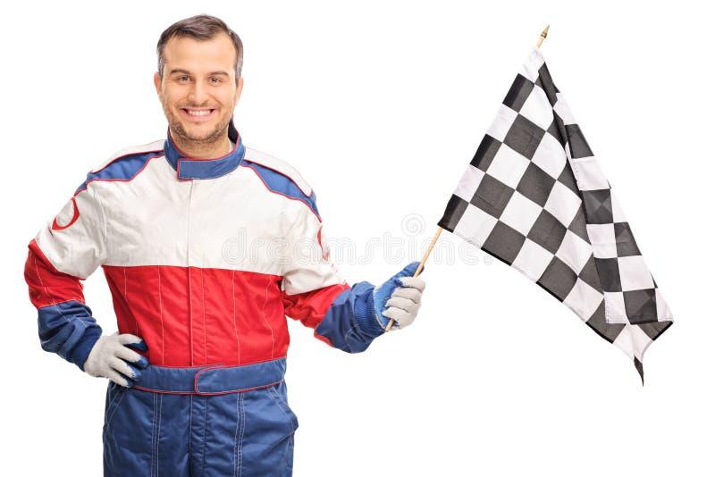 Junger Mann, der eine karierte Rennflagge wellenartig bewegt stockbilder
