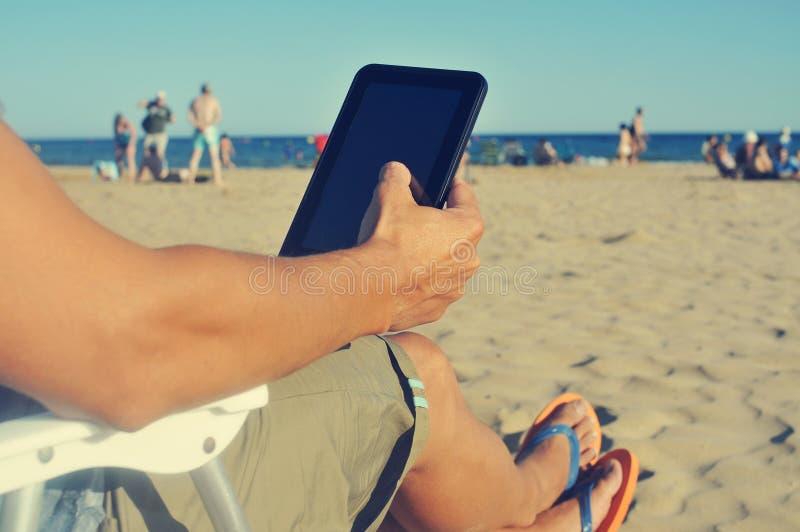 Junger Mann, der eine Tablette auf dem Strand verwendet stockfotos