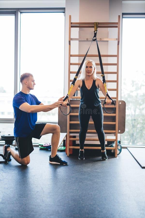 Junger Mann, der eine trainierende Frau unterstützt stockbild