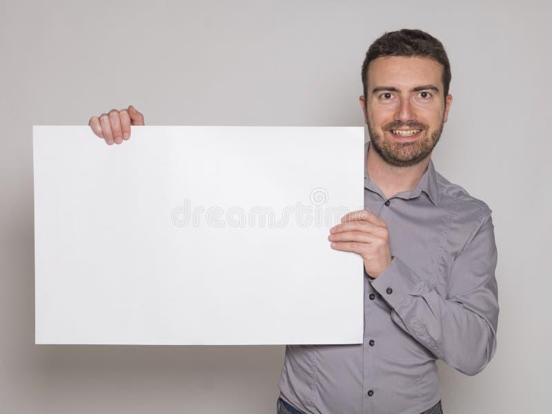 Junger Mann, der eine weiße copyspace Anschlagtafel hält lizenzfreie stockfotos