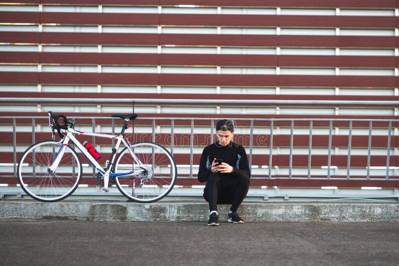 Junger Mann, der in einem dunklen Kleid trägt ein Fahrrad und verwendet einen Smartphone auf dem Hintergrund einer gestreiften Bu stockbild