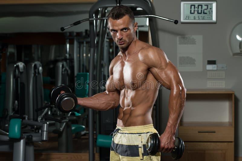 Junger Mann, der in einem Fitnessstudio ausarbeitet lizenzfreie stockbilder