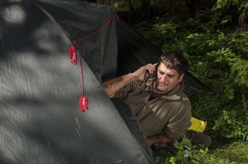 Junger Mann, der an einem intelligenten Telefon in seinem Zelt spricht lizenzfreie stockbilder