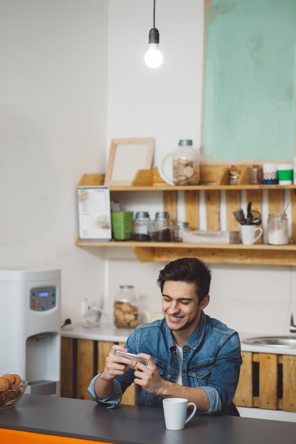 Junger Mann, der an einem Tisch in der Küche mit seinem Handy sitzt stockfotos