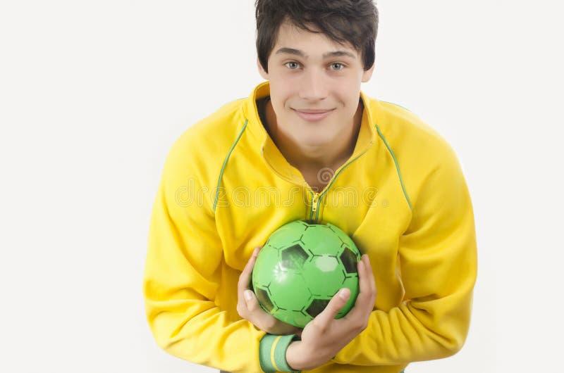Junger Mann, der einen Fußballball fängt stockbild