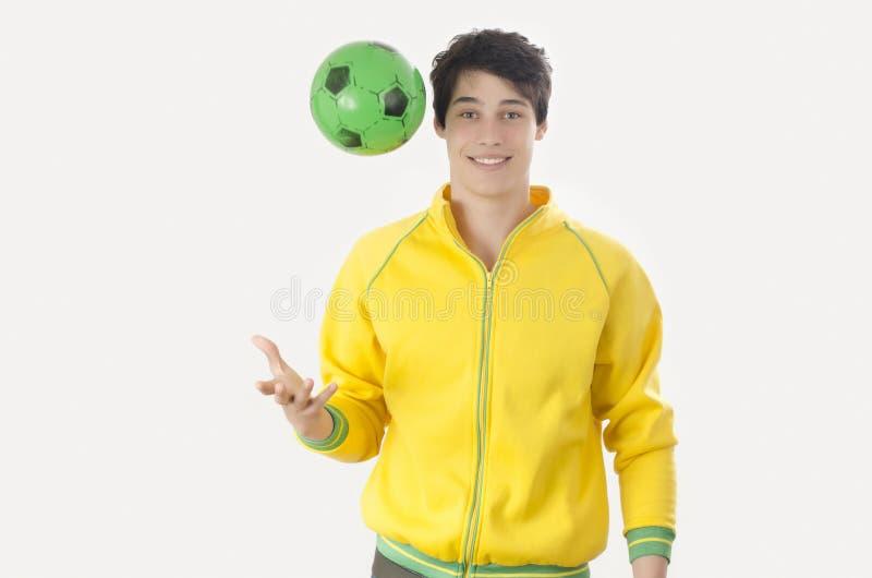 Junger Mann, der einen Fußballball wirft lizenzfreie stockbilder