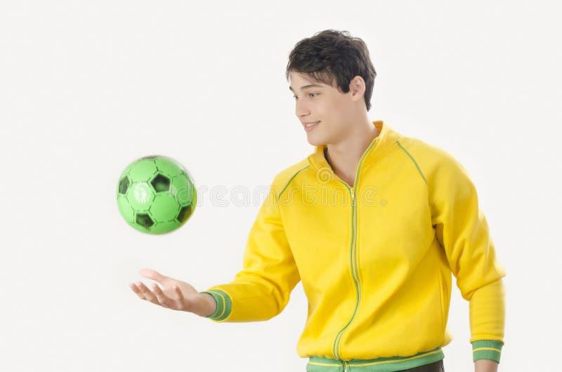 Junger Mann, der einen Fußballball wirft stockfoto