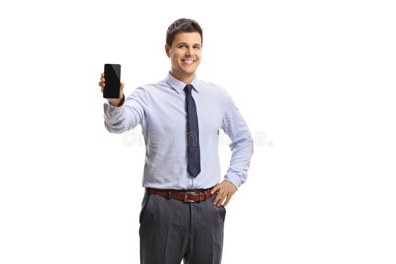 Junger Mann, der einen Handy hält und an der Kamera lächelt lizenzfreies stockfoto